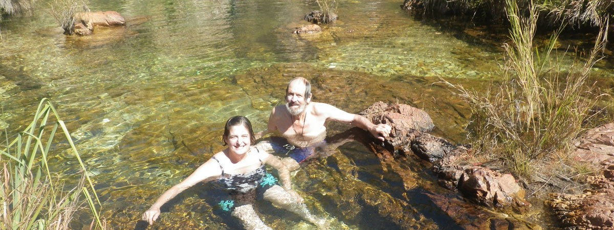 Woman and man swimming above croc creek